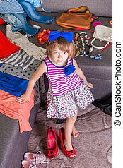 Little girl  wearing  big mother red shoes and bag.  New clothes. Choosing.