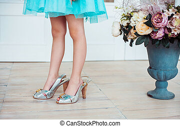 Little girl wearing mother's shoes.