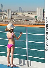 little girl wearing swimming suit and hat is standing on deck of cruise ship and looking at city.