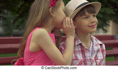 Little girl whispers in boy's ear on the bench