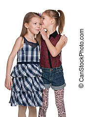 Little girl whispers something to her friend against the...