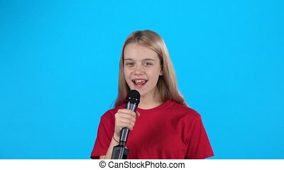 Little girl who smiling and singing with microphone. Slow motion