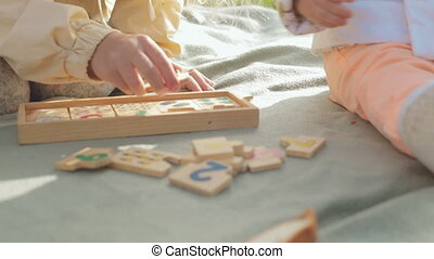Little girl with a baby playing with wooden educational toy on the nature