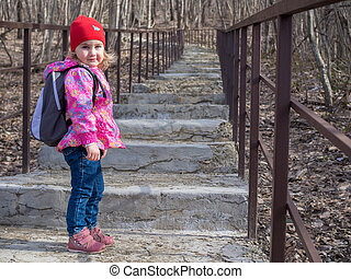 Little girl with a backpack going up the stairs.