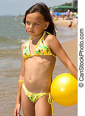 Small girl standing with a ball at the shore of a sea