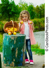 Little girl with a basket of apples