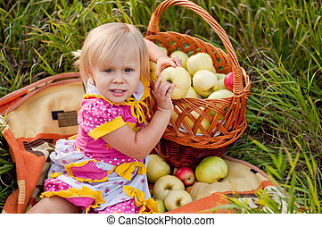 Little girl with a basket of fresh apples