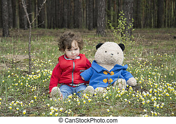 Little girl with a bear in the woods sitting on a flower meadow.