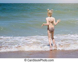 Little girl with a big caution comes in the cool water of the ocean.