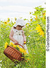 little girl with a big wattled basket with sunflowers