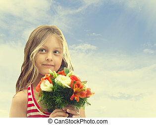little girl with a bouquet of flowers on a background of the sk