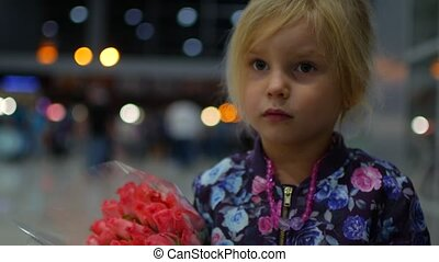 Little girl with a bouquet of roses in the airport lounge