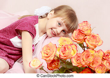 Little girl with a bouquet of tea roses.