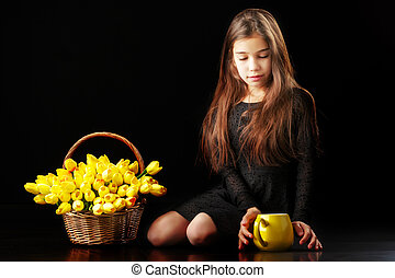 Little girl with a bouquet of tulips on a black background.