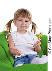 Little girl with a bright lollipop on armchair