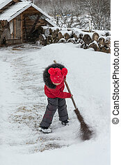 little girl with a broom in winter