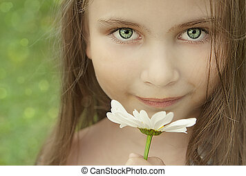 Little girl with a camomile in summer