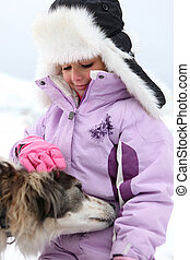 Little girl with a dog in the snow