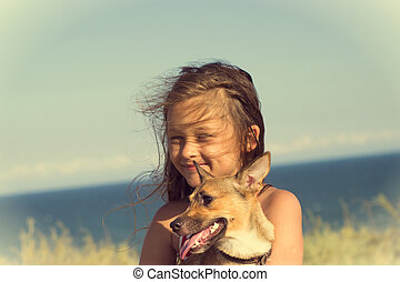 little girl with a dog on the coast