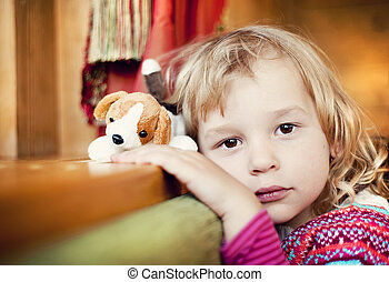 Little girl with a dog toy is leaning on the window