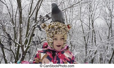 Little girl with a dove on her head in the park