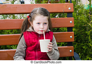 little girl with a drink on a park bench
