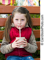 little girl with a drink on park bench