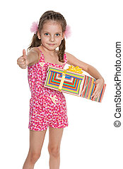 Little girl with a gift box holds her thumb up
