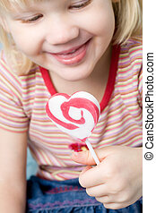 Little girl with a heart shape lollipop
