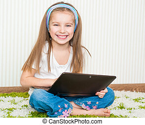 little girl with a laptop - little girl with a tablet at...