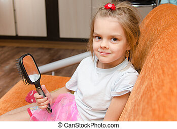 Little girl with a mirror sits on the couch