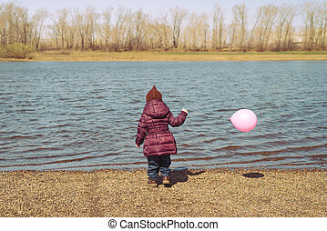 Little girl with a pink balloon on riverbank