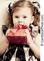 little girl with a red gift box in hands
