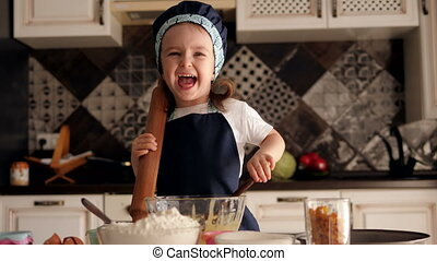Little girl with a rolling pin in her hands is preparing cupcakes in the kitchen