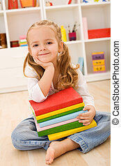Little girl with a stack of books