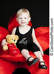 little girl with a teddy bear sitting on red armchair