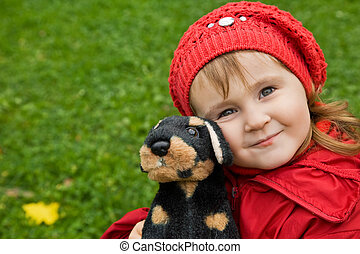 little girl with a toy dog in park