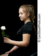 Little girl with a white flower on a black background.