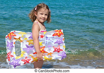 little girl with airbed standing in sea