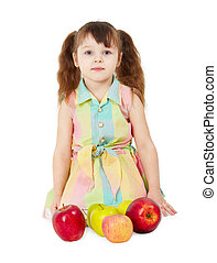 Little girl with apples sits isolated on white background