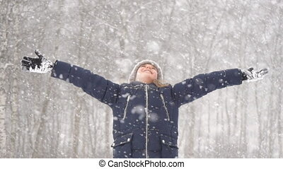 Little girl with arms wide open in snow weather.