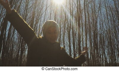 Little girl with arms wide open in the forest.