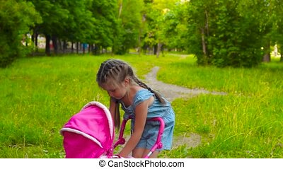 Little girl with baby doll in park