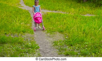 Little girl with baby doll in park with stroller - Little...