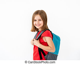Little girl with backpack standing sideways