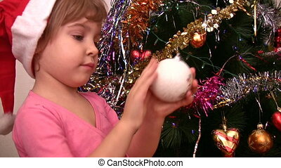 little girl with ball and christmas tree