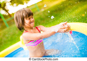 Little girl with ball in the garden swimming pool.