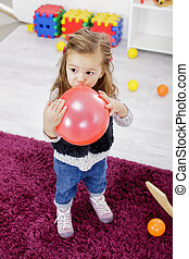 Little girl with balloon in the room