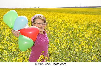 Little girl with balloons on field