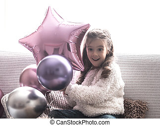 little girl with balloons sitting on the couch